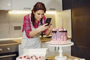 Woman taking a photo of a pink cake she has made