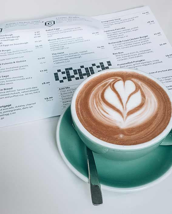 Flat white in a green ceramic cup with the menu for the cafe Crack Kitchen Adelaide