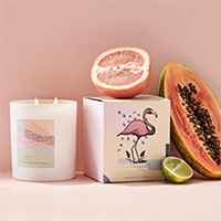 Product photography of Celia Loves candles and fruit props with a pink backdrop