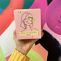 Celia Loves candle in its box with an abstract backdrop