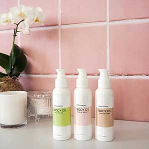 Three white bottles of body oil in front of a pink tile wall