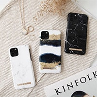 flat lay with three phone cases a magazine and gold jewellery