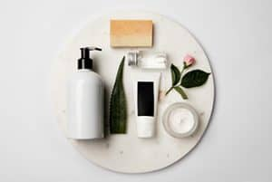 Flat lay of white skincare product bottles with black lids and other items