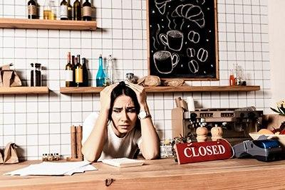 Cafe owner behind her counter stressing over paperwork