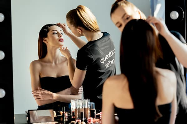 model having her makeup applied by a professional makeup artist