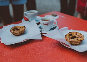 Two espresso cups and two Portuguese tarts