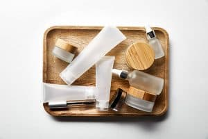 Empty clear cosmetics containers on a wood tray