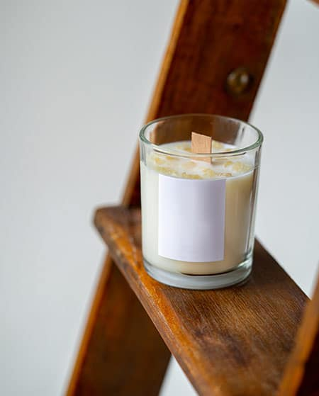 White soy wood wick candle on a wooden ladder