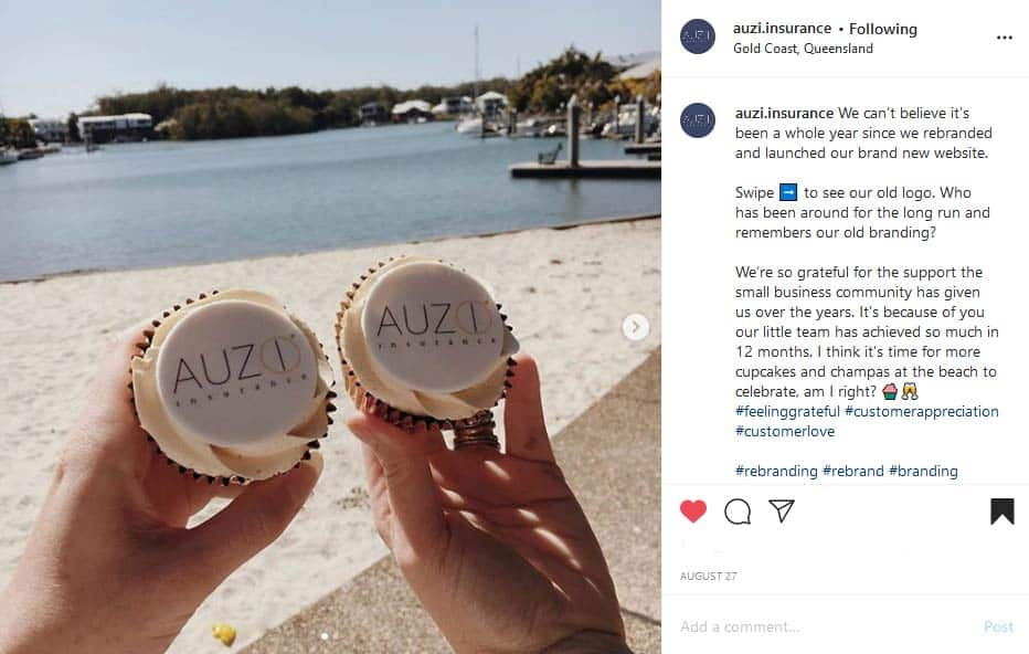 Two white cupcakes with the AUZi Insurance logo on them