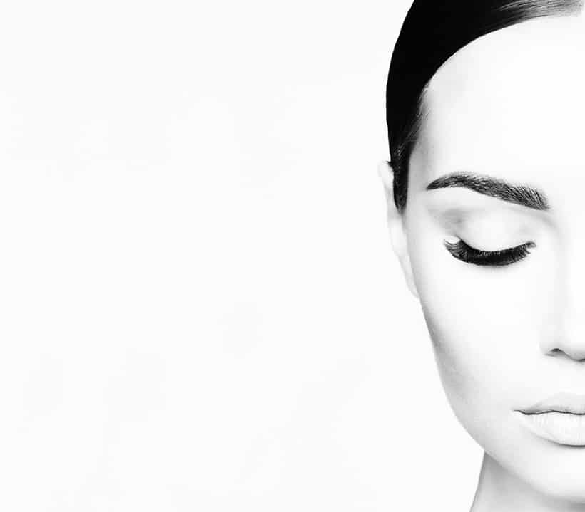 Black and white portrait of half a face showing eyelash extensions.