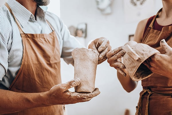 Man and woman making clay crockery