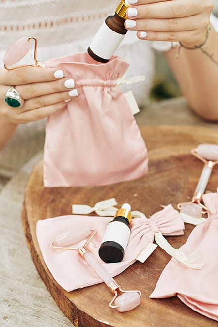 Pink silk bags, quartz face rollers on a wooden table.